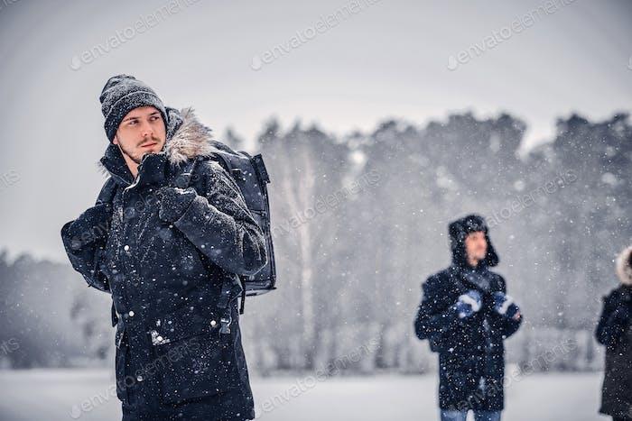 Ein junger Wanderer Typ mit einem Rucksack, der mit seinen Freunden durch einen Winterwald spazieren geht