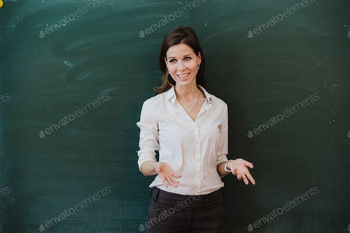 Woman near chalkboard talking to the camera