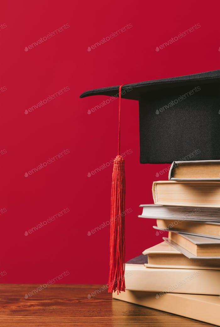 Imagen recortada de la tapa académica en la pila de libros en rojo