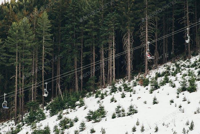 Die Leute heben sich mit dem Skilift in den Bergen
