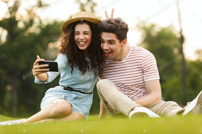 Bild von stilvollen Paar Mann und Frau 20er auf grünem Gras sitzen