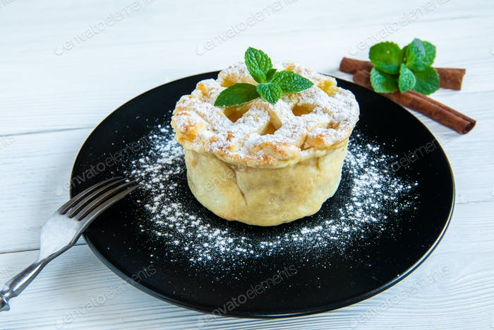 Homemade American Apple Pie Decorated with Powdered Sugar and Mint