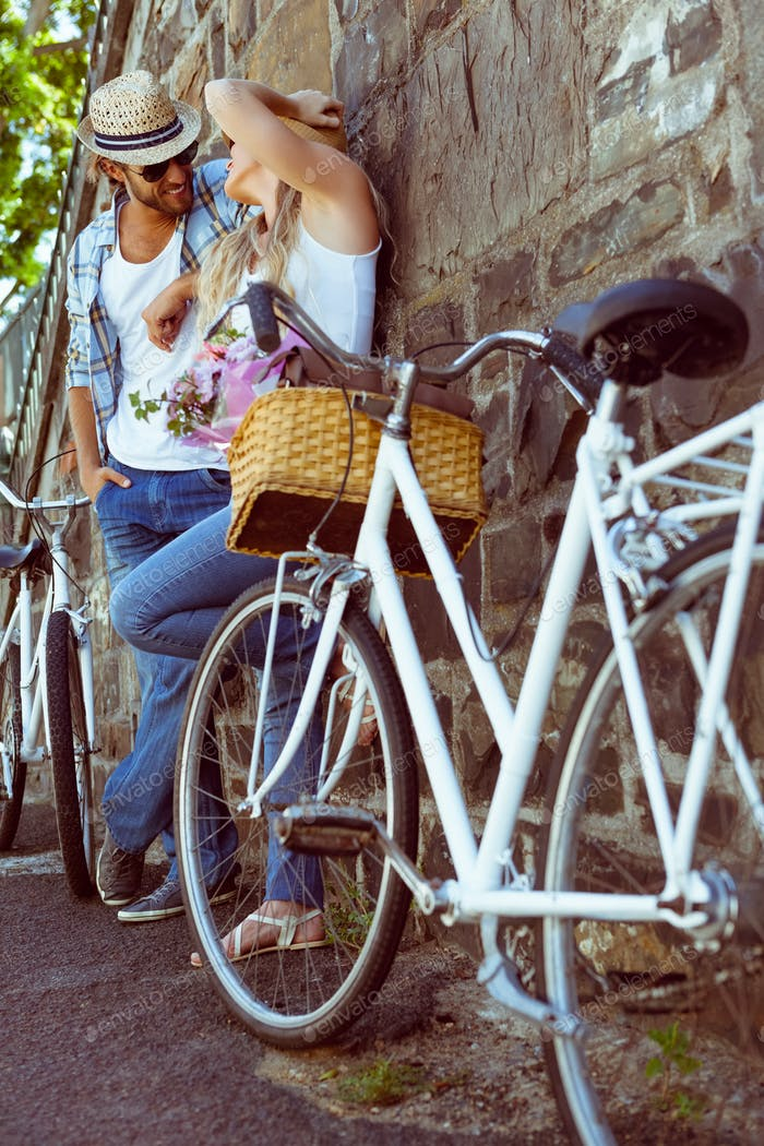 Cute couple with their bikes on a sunny day in the city