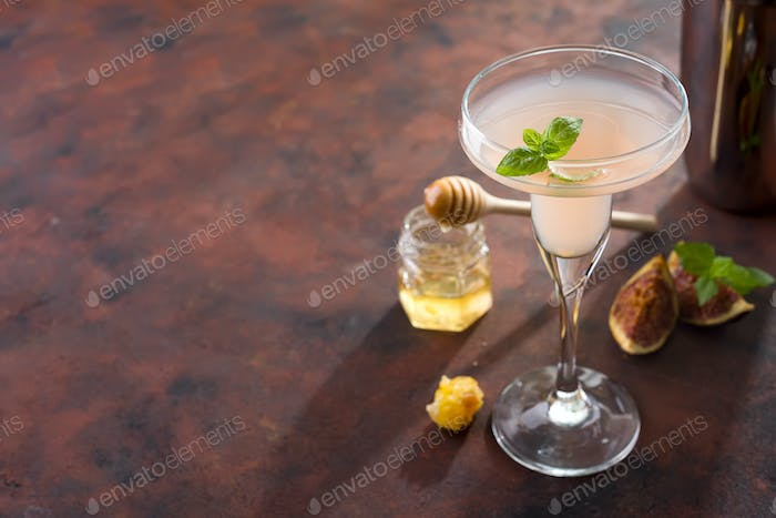 The rose exotic cocktail and figs, honey on brown stone background , copy space