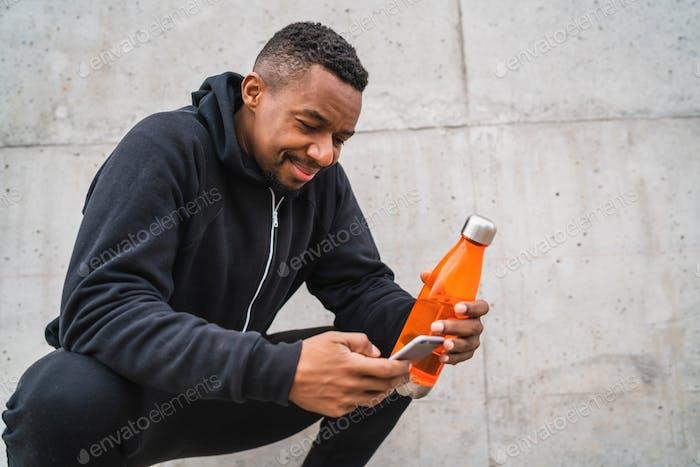 Athletischer Mann mit seinem Telefon nach dem Training.