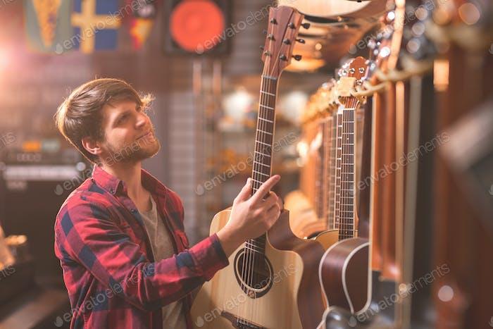 A young man chooses a guitar