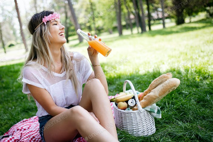 Happy young woman enjoying picnic in park