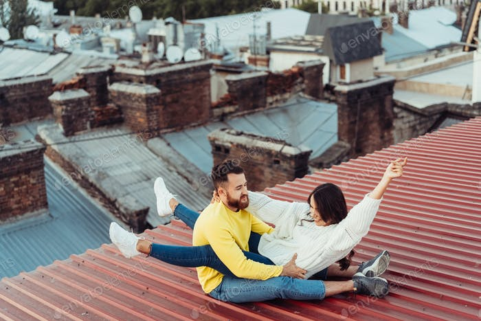 Loving young couple is sitting on the roof of the house