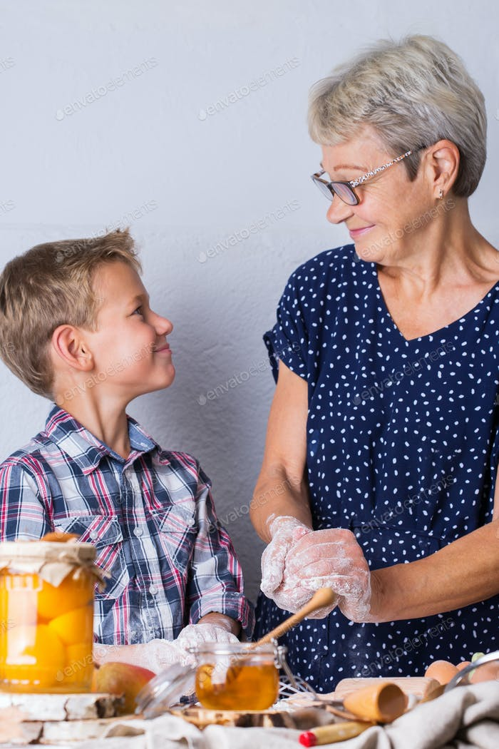 Grandmother with grandson cooking, kneading dough, baking in the kitchen