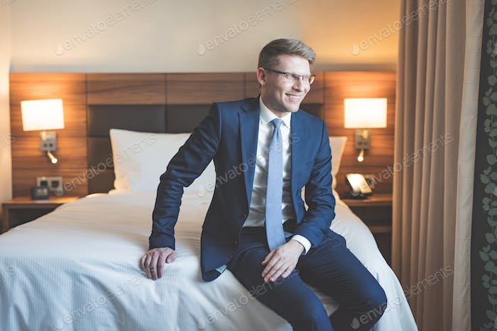 Smiling businessman in a suit in bedroom