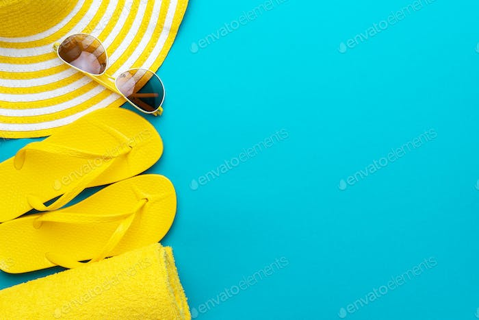 yellow beach accessories on blue background. holiday by the sea concept