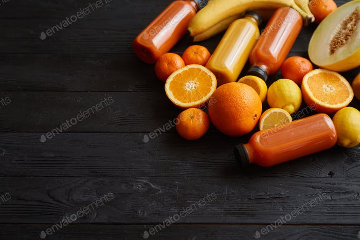 Yellow and orange fruits and botteled juices placed on black wooden background