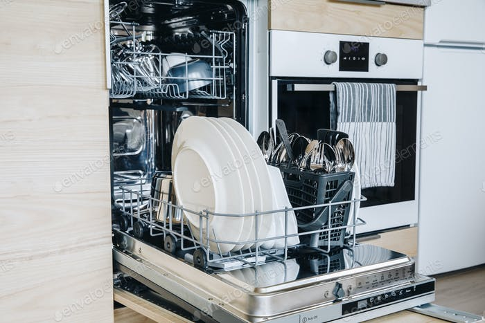 Open dishwasher with white clean dishes after washing in modern scandinavian kitchen.