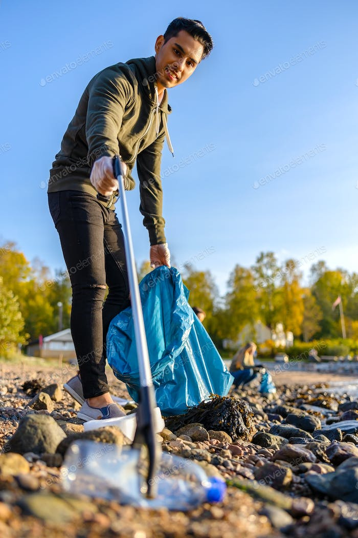 Volunteer picking up garbage with grabber at beach