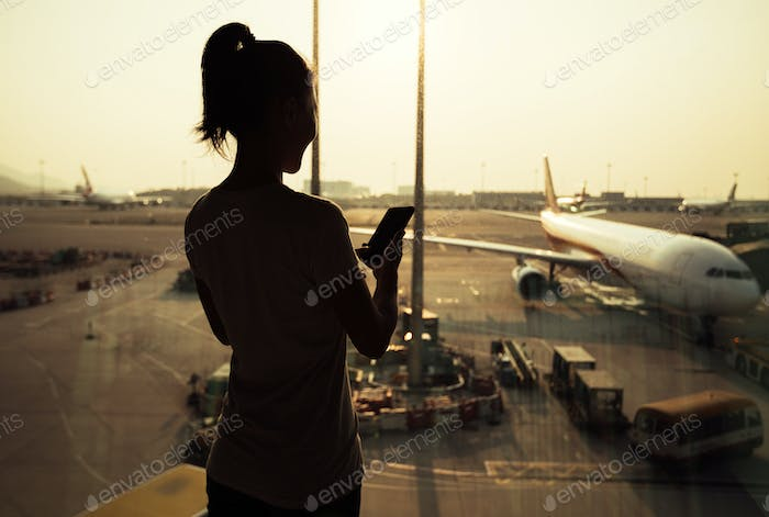 woman using cellphone in airport
