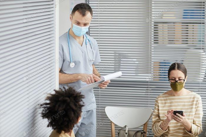 Male Nurse Talking to Patients in Line