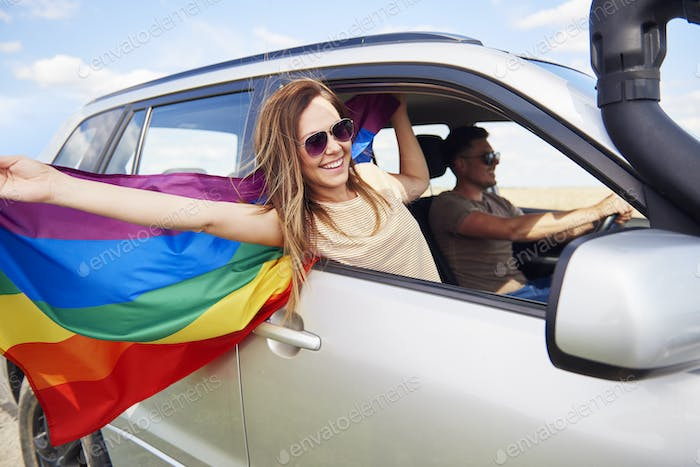 Smiling woman with rainbow flag traveling by car in summertime