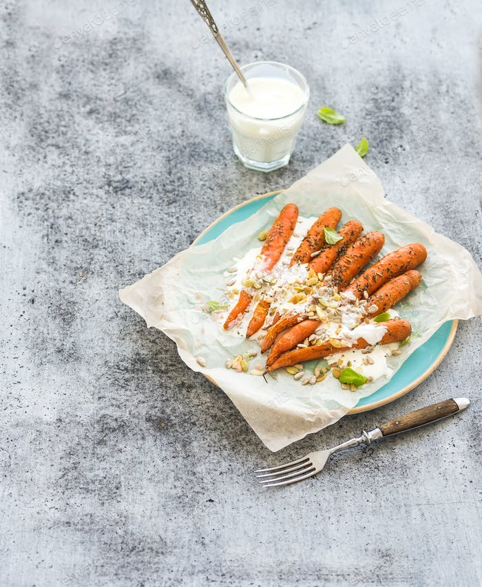 Roasted young carrots with cream and seeds in ceramic plate over grunge grey background