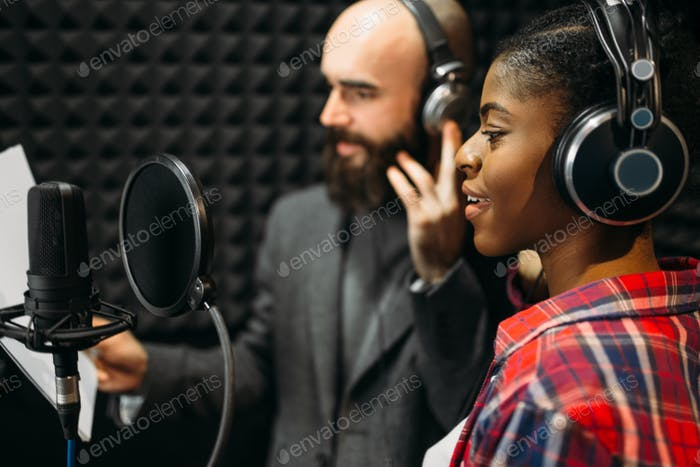Male and female singers in audio recording studio