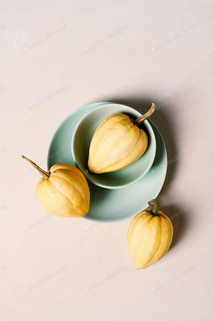 Yellow acorn squashes on the beige textured table
