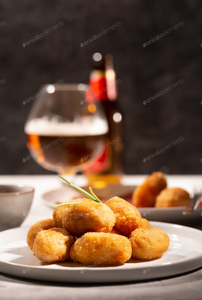 Tapas croquettes, traditional Spanish or French snack with beer on the background