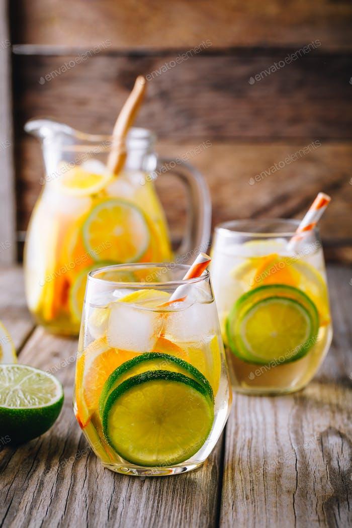 Ein erfrischendes sommerliches eiskaltes Getränk. Weißwein Sangria im Glas mit Limette, Zitrone und Orange