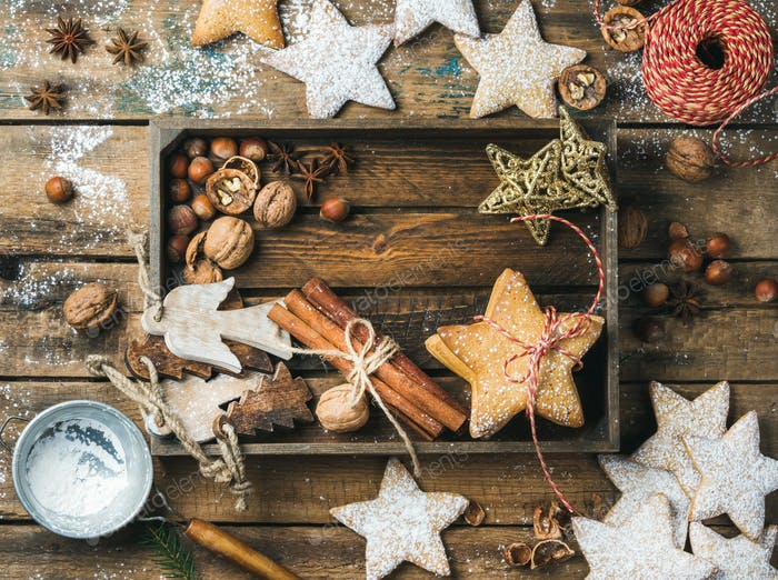 Wooden tray with cookies, decorative angels and stars, cinnamon, nuts
