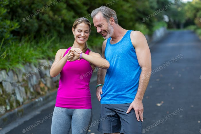 Athletic couple checking time on wristwatch