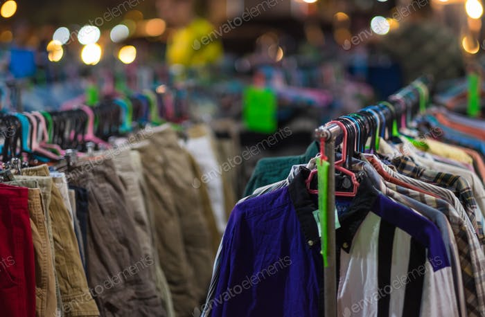 Second hand clothes  are hanging in street market