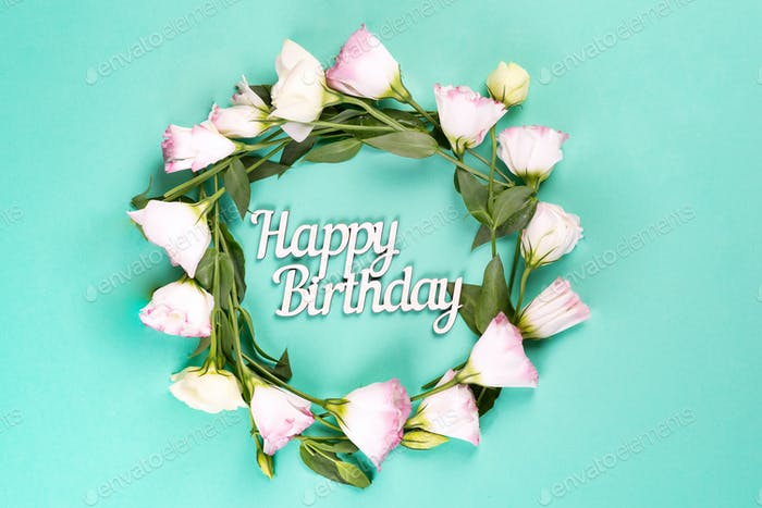 Birthday card. Wreath made of pink flowers eustoma on blue background. Flat lay, copy space