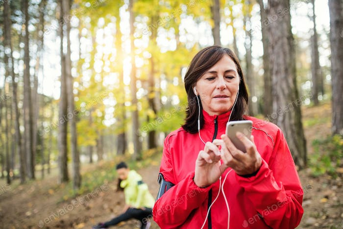 Two female runners with smartphone resting outdoors in forest in autumn nature.