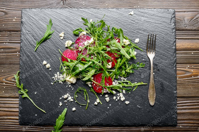 Beetroot arugula and feta cheese salad and fork on slate stone p