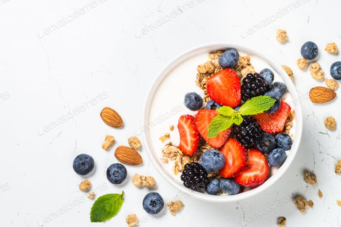 Greek yogurt granola with fresh berries on white table