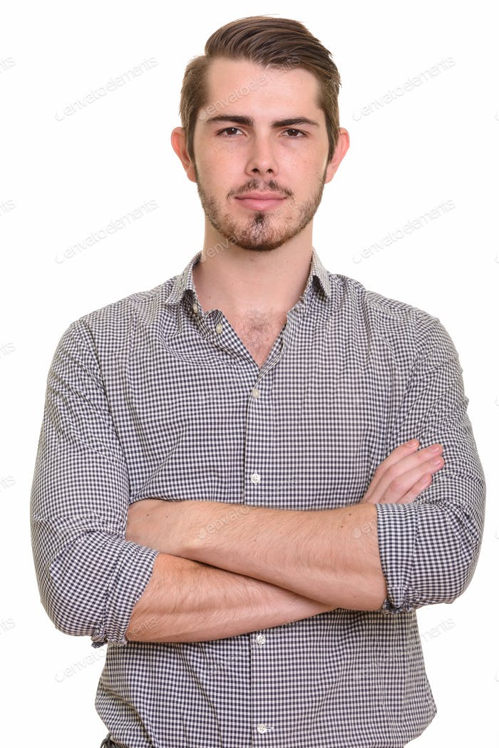 Portrait of young handsome bearded businessman looking at camera