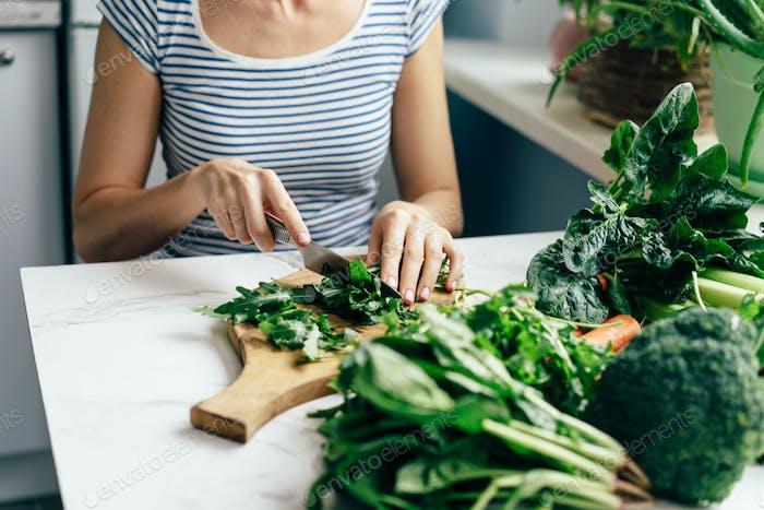 Frau Hausfrau schneidet Grüns für einen gesunden Salat. Frühlingsernte.