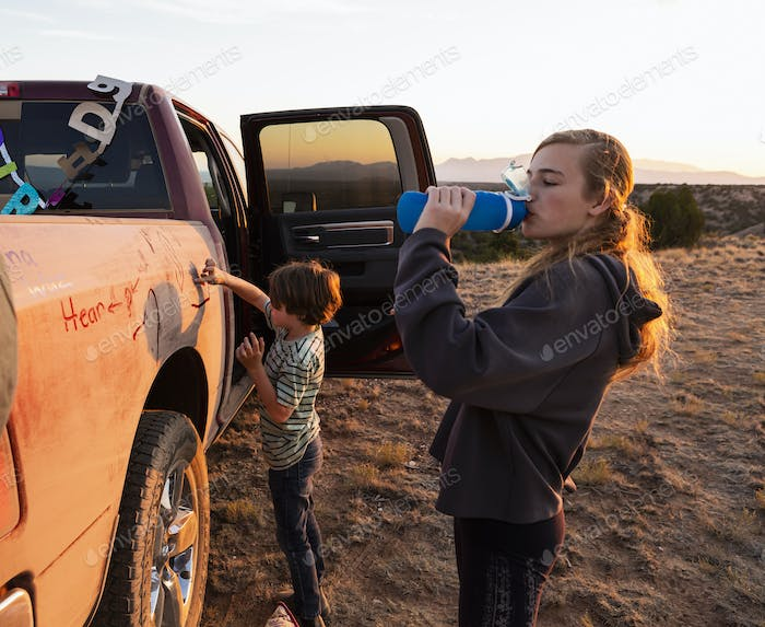 children writing on dirty pickup truck