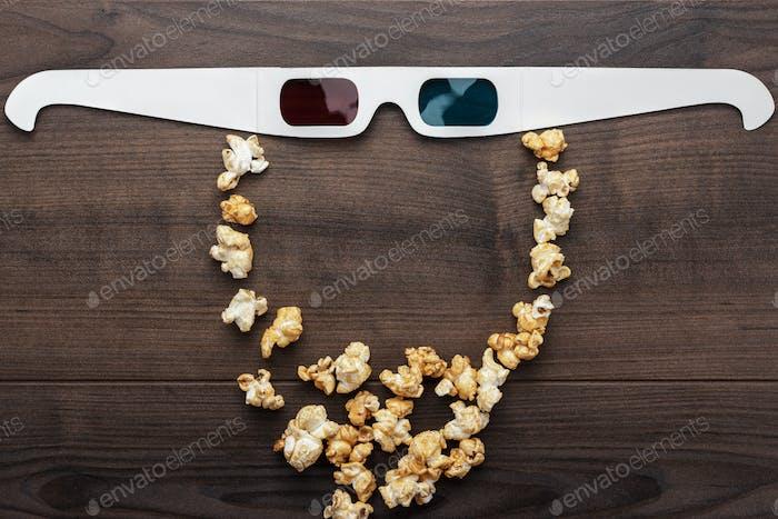 Anaglyph-Gläser und Popcorn machen bärtige Gesicht