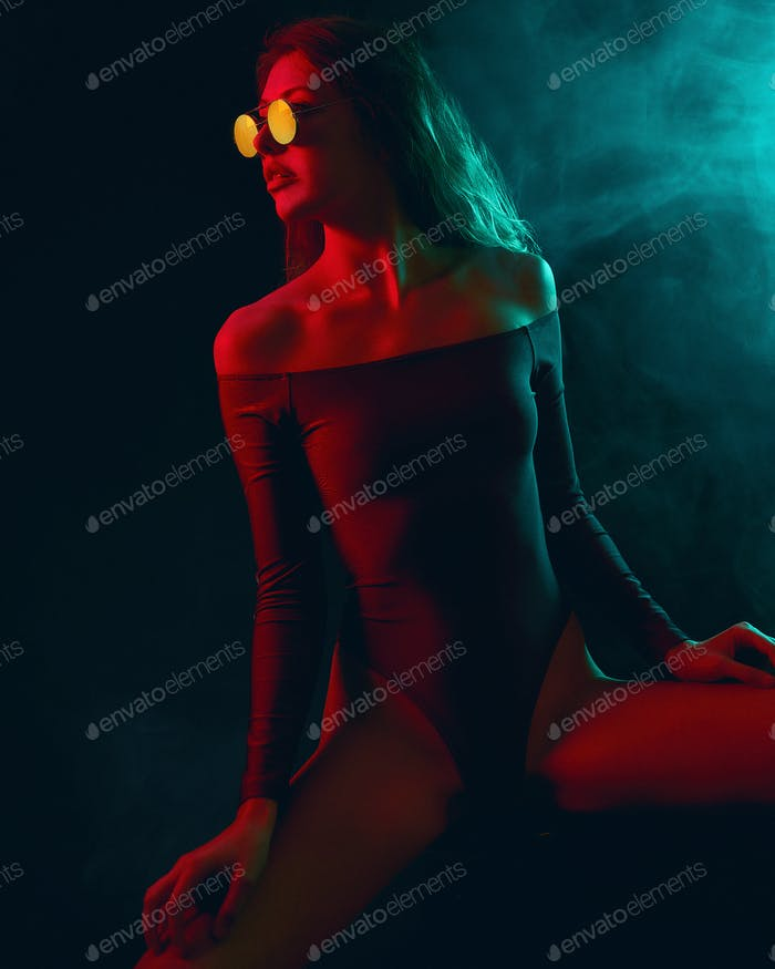 Woman in bikini with sunglasses and blue red lights sitting