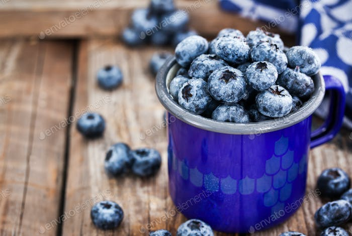 Fresh ripe blueberries and in blue enamel mug