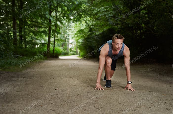 Athletic Man in Running Start Position at the Park