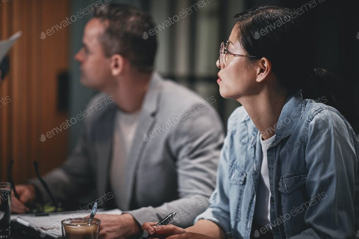 Diverse businesspeople listening to a speaker during a meeting