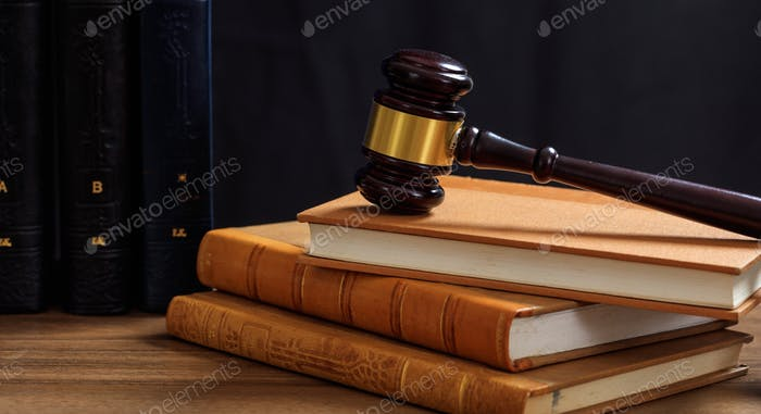 Judge gavel on law books, wooden desk