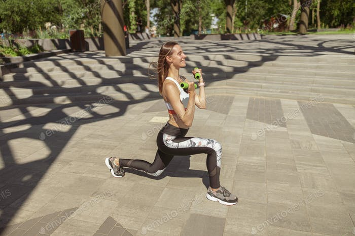 Pretty sports woman in tracksuit does dynamic lunges with dumbbells in park