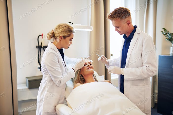 Doctor and assistant doing botox injections on a mature woman