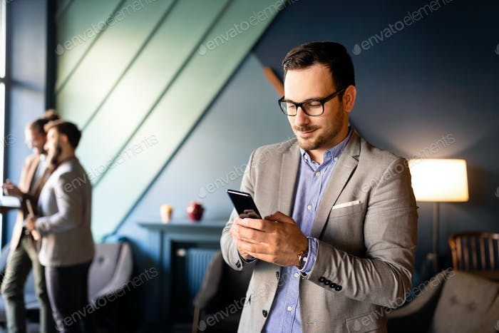 Young handsome businessman using smartphone in the office