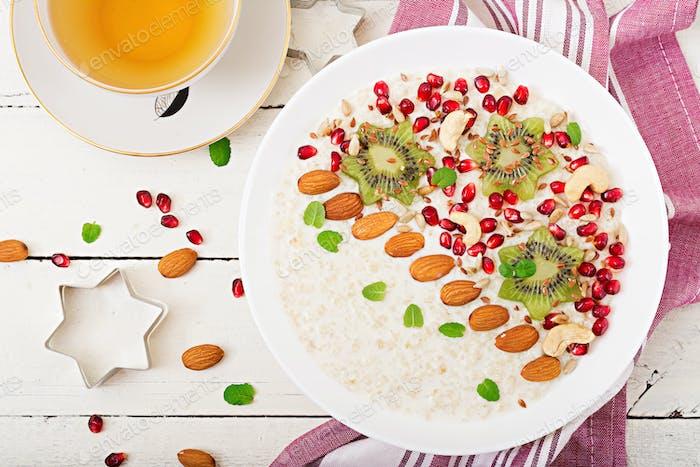Tasty and healthy oatmeal porridge with kiwi, pomegranate and seeds.