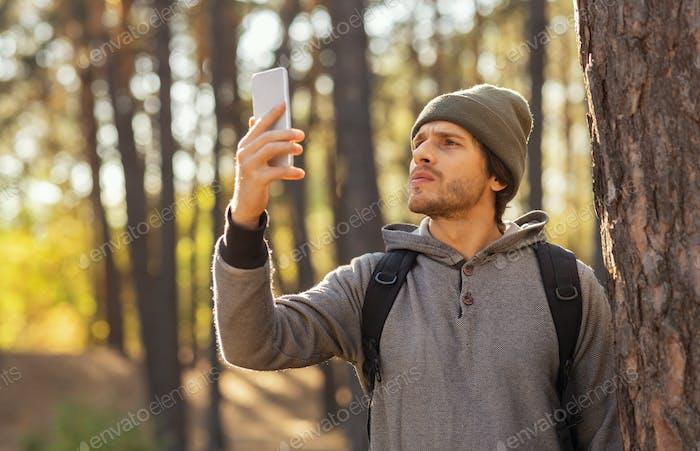 Guy sucht nach mobilem Internet in der Mitte des Waldes