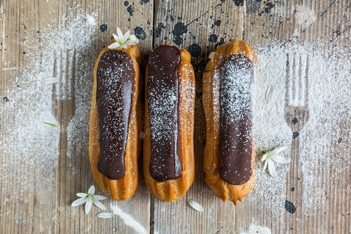 Traditional French dessert. Eclair with chocolate icing in powdered sugar