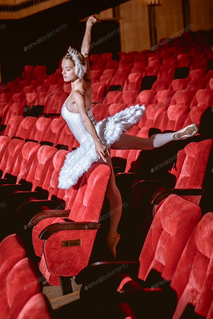 Ballerina sitting in the empty auditorium theater