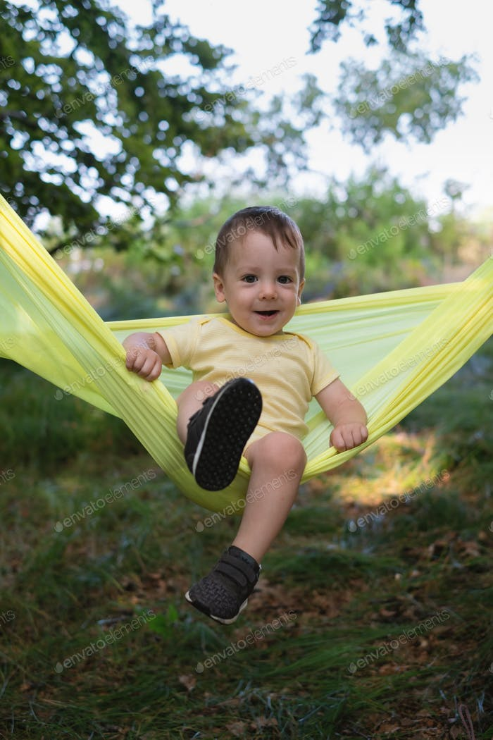 Small kid on yellow hammock in spring forest